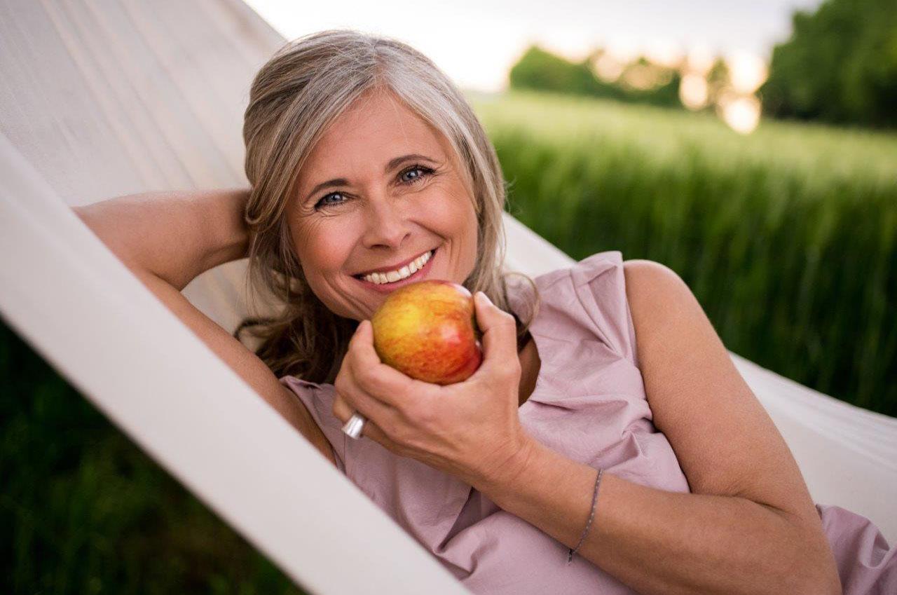 Frau liegt in der Hängematte mit einem Apfel