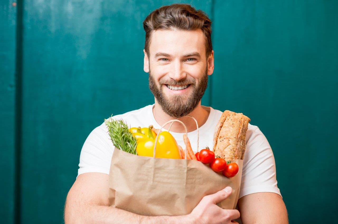 Mann trägt seine Einkaufstüte vor dem Bauch